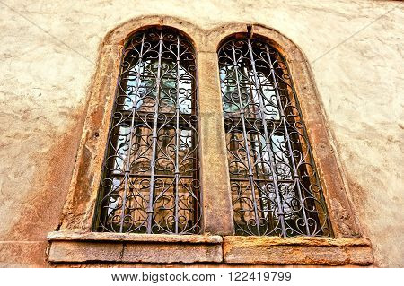 Old window with a grille with a reflection of the church tower on the glass useful as a background