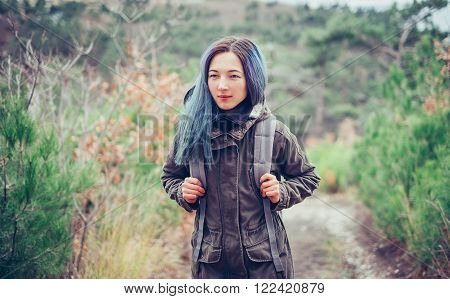 Hiker girl wearing in parka jacket with backpack walking in the forest front view