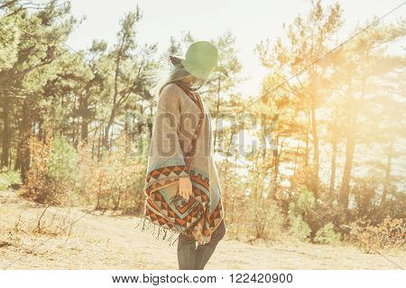 Fashionable young woman in hat and poncho walking in forest among pine trees at sunny day