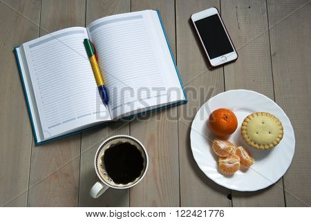 Open day planner, smartphone,  ballpoint pen, cup of coffee, cake and mandarin on a plate on the wooden table
