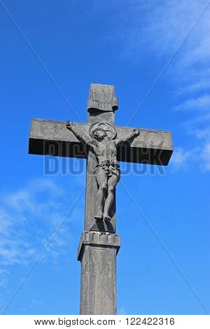 Stone Crucifix against a blue sky in Volvic