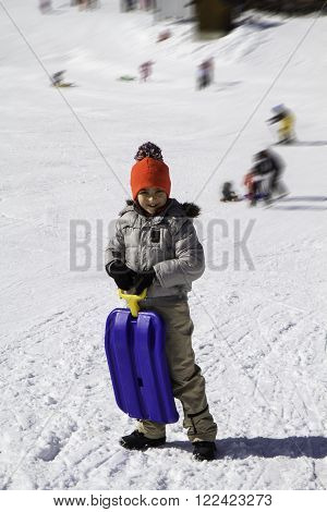 child in the snow with blue toboggan and hat with pom poms
