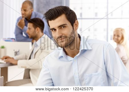 Closeup portrait of handsome young businessman looking at camera, smiling.