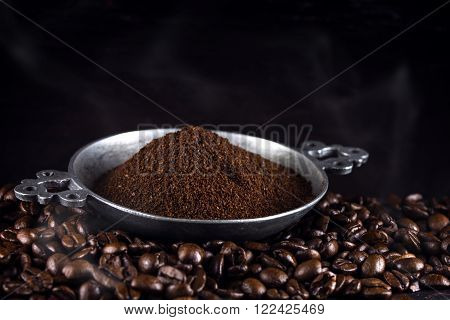 ground coffee in a metal cup on freshly roasted coffee beans against a dark brown background, selected focus, narrow depth of field