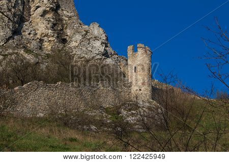 Ruins of the former famous fortress Devin castle Bratislava Slovakia. Surrounding wall with a tower. Bright blue sky.