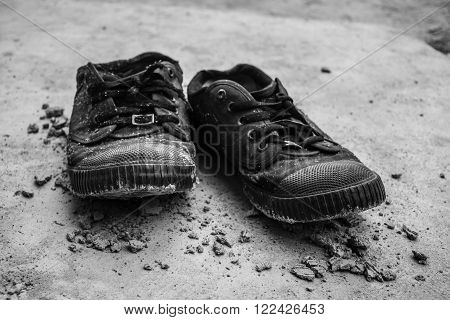 Shoes stained soil is black and white.