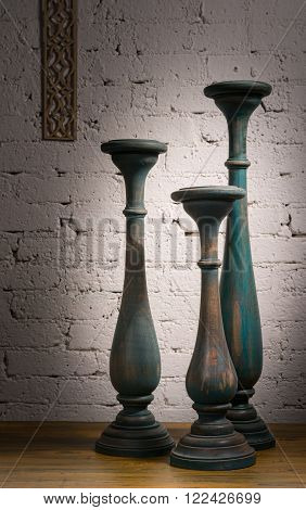 Composition of three blue gray vintage wooden candlesticks on a background of wooden floor and white painted brick wall