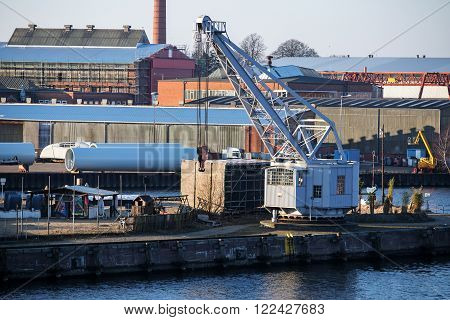 cargo port scene with an old dockyard crane on the pier.