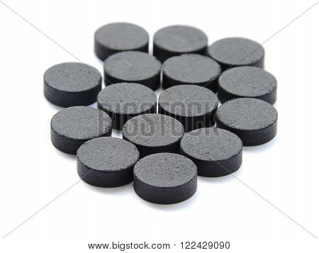 Closed up Activated charcoal carbon pills isolated on white background