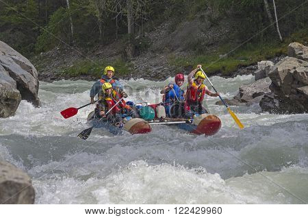 CHUYA RIVER RUSSIA - AUGUST 7 2014: Sports catamaran in the middle of a difficult rapids. River Chuya Altai. Tourists call this rapids as