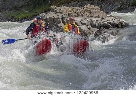 CHUYA RIVER RUSSIA - AUGUST 7 2014: Extreme rafting. Sports catamaran in a difficult rapids. River Chuya Altai. Tourists call this rapids as