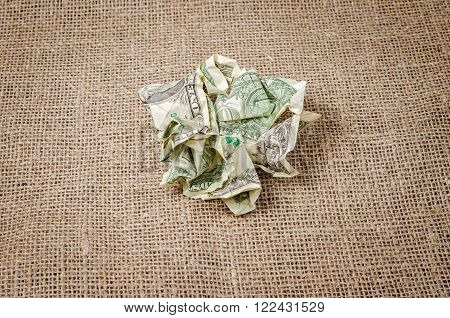 US dollar banknotes crumpled on rustic jute background