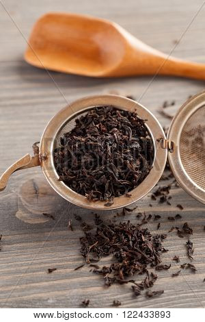 Black tea in metal strainer on a wooden table with wooden spoon selective focus vertical closeup shot