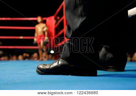 Junior kick boxer on the boxing ring : lower view from the boxing judge corner. (focus on referee)