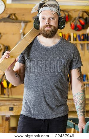 Portrait of smiling and confident carpenter using band saw for cutting wood in a workshop for woodwork. Man with tattoo and beard using safety mask with visor and earmuffs.