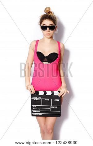 Stylish fashionable blonde girl hipster posing in studio on a white background holding a clapperboard in his hands