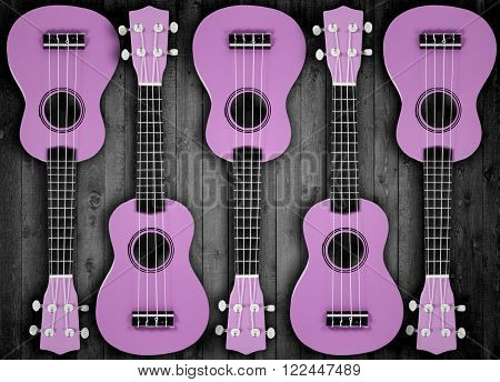 A number of purple acoustic guitars on the wood background.