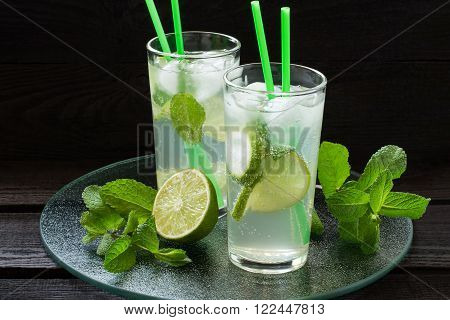 Mojito cocktail with rum lime mint and soda in a highball glass on a glass tray