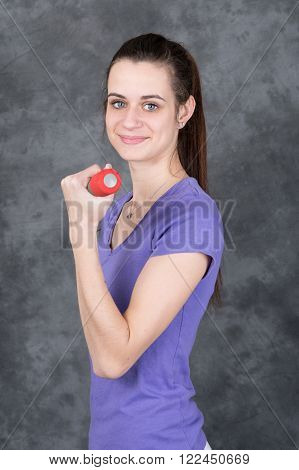 Young Woman doing fitness exercise with a hand weights on grey