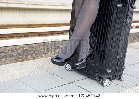 close-up of woman in high heels sitting on suitcase at train station