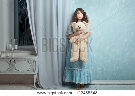 Plump woman hugging toy bear she stands near a wall like a little girl.