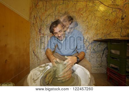 man shaping a clay pottery bowl on wheel