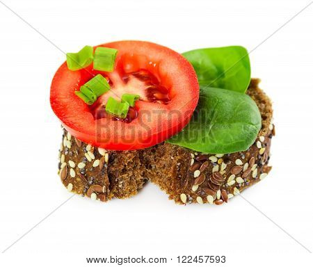 Small sandwich with tomato, spinach and onion isolated on white background.