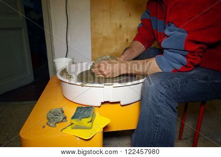 hands shaping a clay pottery bowl on wheel