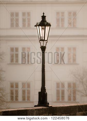 Street lamp on Charles Bridge in foggy morning, Prague, Czech Republic. Sepia image.