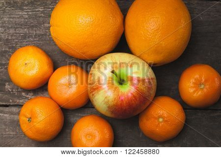 Apple and citrus on a background of a wooden table