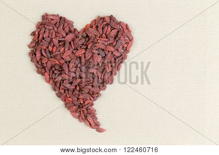 Heart shape formed of healthy dried goji berries or wolfberries on a textured cream colored background with copy space conceptual of good health and diet