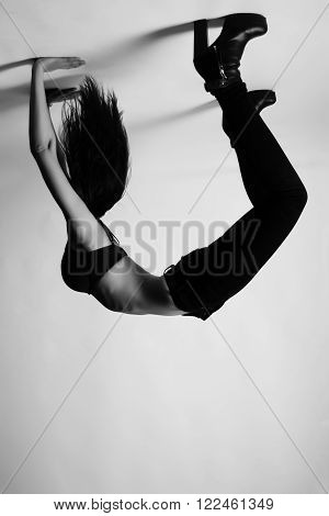 Brunette in bridge pose upside down, wearing bra and high heels. Black and white shot indoors