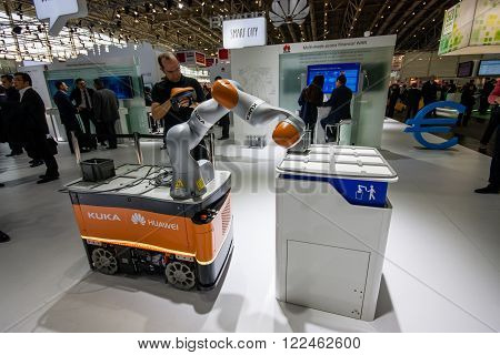 HANNOVER GERMANY - MARCH 14 2016: Industrial KUKA robot in booth of Huawei company at CeBIT information technology trade show in Hannover Germany on March 14 2016.