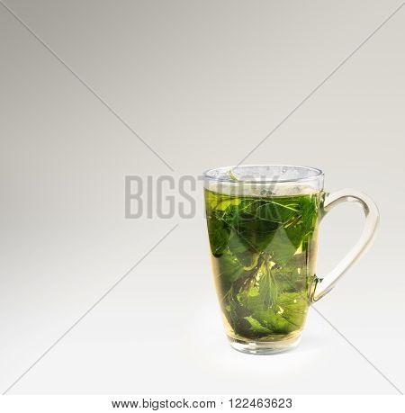 Tea glass with dried nettle tea in a grey background