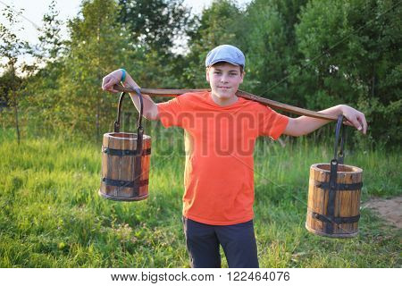 Portrait of a young boy in a cap with a yoke and wooden pails