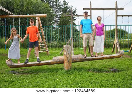 Parents with son and daughter swinging on a swing on a wooden playground