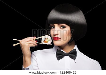 Woman with bob cut hair holding sushi with chopsticks isolated on black