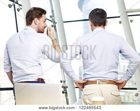 rear view of two caucasian business people looking out of window talking in office.