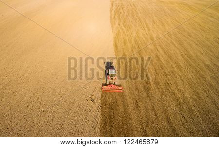 Aerial view of ploughed field with tractor sowing seeds of wheat. Industrial background on agricultural theme.