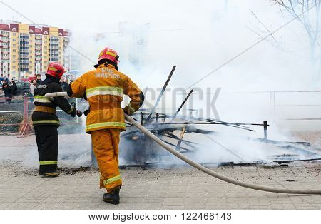 GOMEL BELARUS - MARCH 12 2016: Employees of Ministry of Emergency Situations extinguish the remnants of Shrovetide scarecrow after his ritual burning during of Shrovetide celebration
