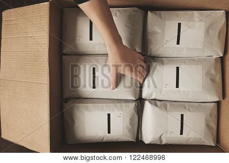Hand Put Blank Package In Big Craft Carton Box