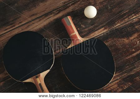 Two professional ping pong rockets lying on vintage wooden table. Black antispin pads. One attack plus, other defense, japan and german made. White ball is near.