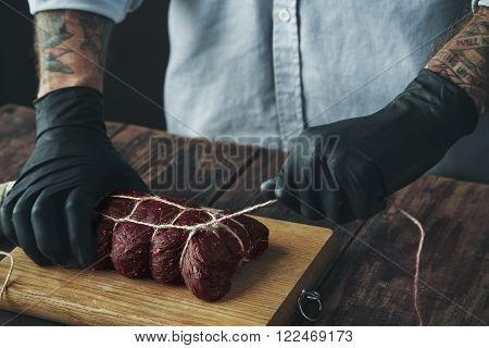 Tattooed Butcher Ties Meat With Rope To Smoke Wooden Table