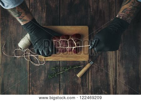 Tattooed Butcher Ties Meat With Rope To Smoke Top View