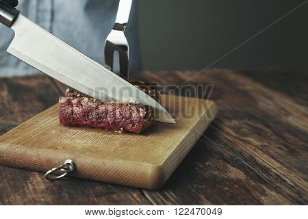 Knife Cut Slice Of Grilled Meat On Wooden Board