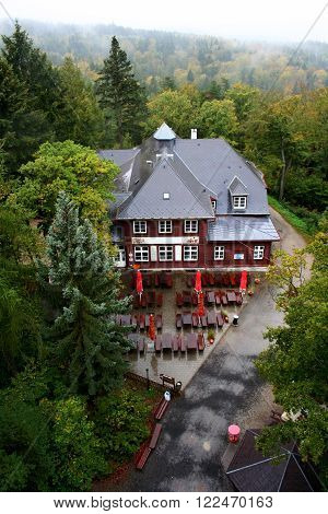 Top view of small cafe in autumn forest in fog near Karlovy Vary Czech Republic.