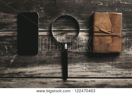 Mobile smartphone magnifier and notebook with leather cover isolated on black farm wooden table Mysterious detective game concept.