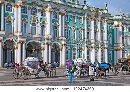 SAINT - PETERSBURG, RUSSIA - MARCH 20, 2016: People near coaches with horses on The Palace Square. On the background is The State Hermitage Building.