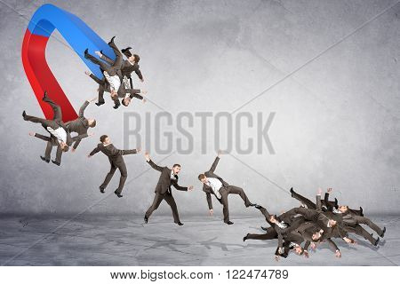 Businessmen attracted within magnet on grey wall background, business concept
