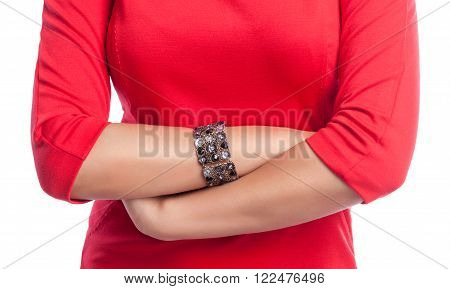 Closeup on crossed hands of business woman wearing a red dress. White isolated background.